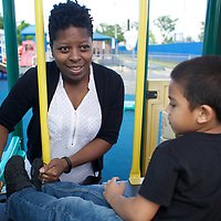 Supportive Housing program case worker, Melissa spends time at a Hartford playground with Joels, age 5. Melissa is Supportive Housing program case worker to Joel's mother Irma. Melissa has provided support to Irma for over two years. <br /> <br /> Irma, age 24, left home at the age of nine after she and her brother suffered abuse at the hands of their step father. After several years in the care of foster homes and living homeless, Irma became pregnant at age 15. By the age of 23, Irma had lived through periods of homelessness and had become mother to four children with two different men, both of whom were abusive. Six months into her fourth pregnancy, Irma's partner threw her down the stairs and she went into premature labour. Medical staff told Irma that she would miscarry but her youngest son, Julio survived after spending the first six months of his life in hospital. The sustained involvement of medical professionals in Irma's life alerted the Supportive Housing program to her situation. Case worker Melissa began working with Irma, offering support, advice and providing the funds to purchase items for the care of baby Julio. Melissa made representations to the Department of Children and Families (DCF) to vouch for Irma's character and convince them that Irma should not be separated from her children. Melissa encouraged Irma to go back to school and complete her high school diploma. <br /> <br /> Supportive Housing  provided Irma a housing-voucher so that she could keep her children and live independently of her abusive partner. Irma now lives with her children who have rooms of their own and a back yard in which to play. Julio, now eighteen months, has significant health needs but the relative stability of Irma's life now means she can look to the future with a sense of optimism. She hopes to complete her associates degree in nursing and eventually earn an income that will allow her to live in accommodation without the need of a subsidy from Supportive