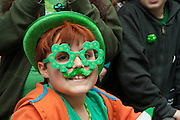 A boy in green glasses watching the parade.