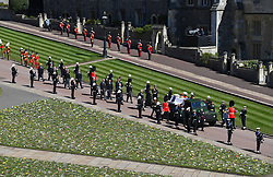 The Duke of Edinburgh's coffin, covered with his Personal Standard, is carried on the purpose built Land Rover Defender followed by the Princess Royal, the Prince of Wales, the Duke of York, the Earl of Wessex, the Duke of Cambridge, Peter Phillips, the Duke of Sussex, the Earl of Snowdon, Vice Admiral Sir Timothy Laurence outside St George's Chapel, Windsor Castle, Berkshire, ahead of the funeral of the Duke of Edinburgh. Picture date: Saturday April 17, 2021.