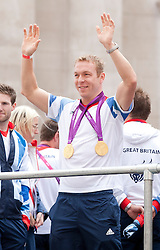 © Licensed to London News Pictures. 10/09/2012. LONDON, UK. Cyclist Sir Chris Hoy waves at spectators whilst wearing the two gold medals he won at the 2012 London Olympics near Bank Station during a parade for Olympic and Paralympic athletes in London today (10/09/12)  . Photo credit: Matt Cetti-Roberts/LNP