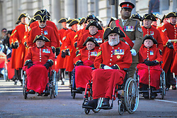 © Licensed to London News Pictures. 12/11/2017. London, UK.  Lance Sergeant Johnson Gideon Beharry, VC, CNG, pushes a Chelsea Pensioner in a wheelchair on their way to Horse Guards parade on Remembrance Sunday where members of the Royal Family, dignatories and veterans gave tributes to war dead at The Cenotaph.  Photo credit: Stephen Chung/LNP