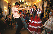 """Everyone wearing traditional dress, men """"traje corto"""" and women frilly flamenco dresses. Daytime festivities, eating, dancing, meeting friends and business contacts in the """"casetas"""" temporary marquee tents, set up during the Feria..The Feria de abril de Sevilla, """"Seville April Fair"""" dates back to 1847. During the 1920s, the feria reached its peak and became the spectacle that it is today. It is held in the Andalusian capital of Seville in Spain. The fair generally begins two weeks after the Semana Santa, Easter Holy Week. The fair officially begins at midnight on Monday, and runs six days, ending on the following Sunday. Each day the fiesta begins with the parade of carriages and riders, at midday, carrying Seville's citizens to the bullring, La Real Maestranza...For the duration of the fair, the fairgrounds and a vast area on the far bank of the Guadalquivir River are covered in rows of casetas (individual decorated marquee tents which are temporarily built on the fairground). Some of these casetas belong to the prominent families of Seville, some to groups of friends, clubs, trade associations or political parties. From around nine at night until six or seven the following morning, at first in the streets and later only within each caseta, crowds of people party and dance Sevillanas, traditional Flamenco dances, Sevillan style drinking Jerez sherry, or Manzanilla wine, and eating tapas. Men and women dress up in their finery, the traditional """"traje corto"""" (short jacket, tight trousers and boots) for men and the """"faralaes"""" or """"trajes de flamenca"""" (flamenco style dress) for women. The men traditionally wear hats called """"cordobés""""."""