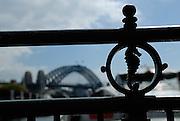 Seahorse motif in wrought-iron railing, with Sydney Harbour Bridge in background. Circular Quay train station, Sydney, Australia