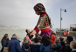 © Licensed to London News Pictures. 19/10/2021. Folkestone, UK. British actor Jude Law greets Little Amal, a giant puppet, as she performs on the Harbour Arm at Folkestone in Kent. The 3.5m tall puppet, worked by a team of puppeteers, has been on a journey starting from Turkey in July, visiting Greece, Italy, Switzerland, Germany, Belgium and France.  Little Amal, whose name means hope in Arabic, represents the journey of a nine year old girl from Syria. Photo credit: Peter Macdiarmid/LNP