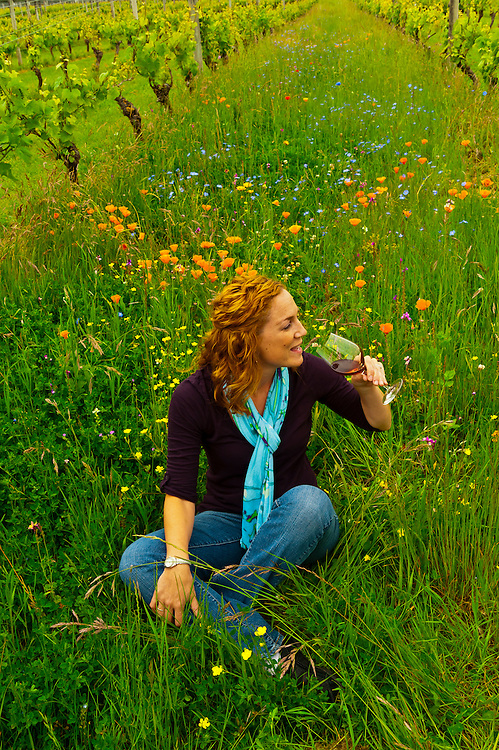 A guest sits surrounded by the wildflowers growing between the rows of vines and sips a glass of wine, Martinborough Vineyard, Martinborough, South Wairapa region, North Island, New Zealand
