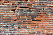 Close up of a weathered brick wall with masonry imperfection