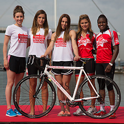 © Licensed to London News Pictures. 27/07/2013. London, UK. Jade Jones, Charlie Webster, Melanie C, Zoe Hardman and Nicola Adams pose with a bicycle at the London Triathlon 2013 at the ExCel centre in Royal Victoria Dock in East London. Photo credit : Vickie Flores/LNP