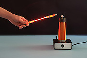 The strong electric fields created by the tesla coil cause the gas in a neon emission tube to glow.