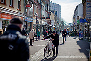People are waiting in the shopping street in Oberursel in times of social distancing because of the corona virus.