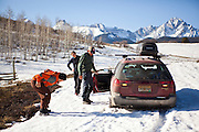 Backcountry skiers get their car stuck in snow up an unplowed road in the San Juan Mountains, Colorado.