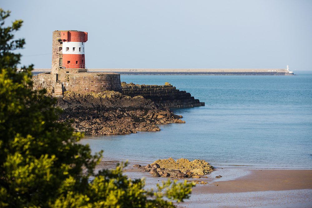 Archirondel Tower and beach, bathed in sunlight on a calm day with St Catherine's breakwater in the distance, in Jersey, Channel Islands