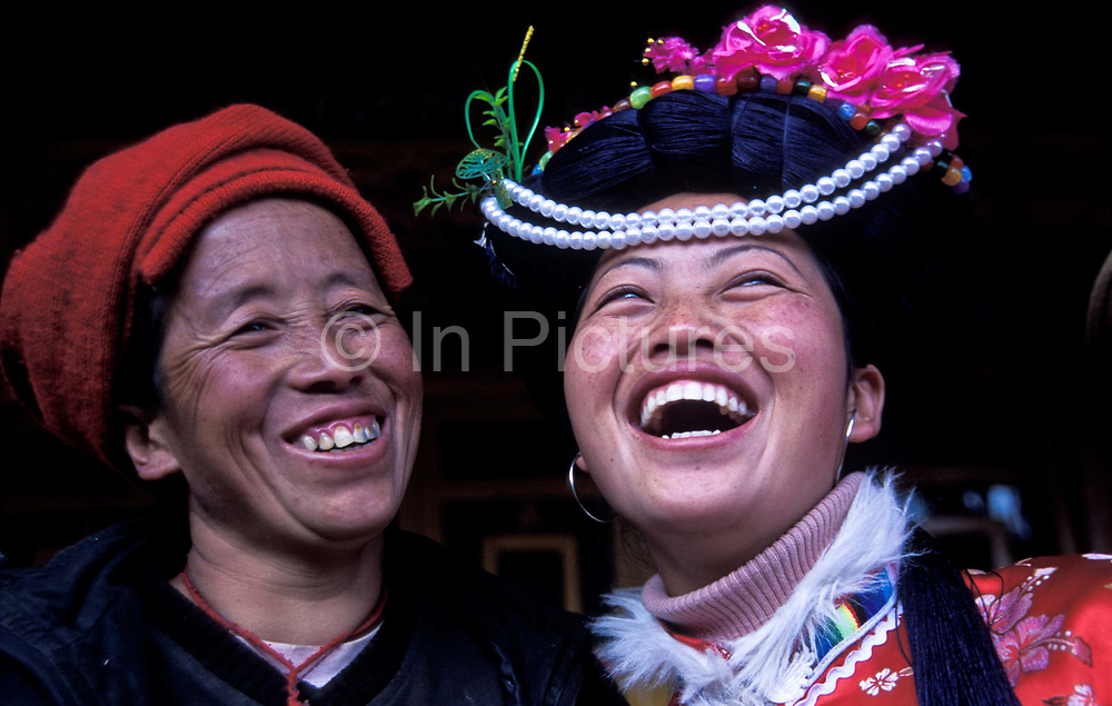 """Mu Ze Latso, 22, shares a joke and an intimate moment with her mother Mu Ze Namu, they belong to the Mo Suo minority / tribe from Lugu Lake, northwest Yunnan province.<br /> <br /> Mo Suo people live along LuGu lake, northwest  Yunnan province. Since the population is not big enough, the Chinese government did not assign them as an independent minority. Mo Suo people belongs to the NaXi minority of LiJiang region. Mo Suo people have their own distinctive culture, religion and customs. Most significantly: Mo Suo people do not have a marriage System. Locally, they call their relationships a """"walking marriage"""". <br /> A girl has her ADULT ceremony when she is 14, then she can start to wear the Mo Su costume and the family will give her a room that is called """"Flower room"""".<br /> Logically, she is allowed to take her boyfriend, since Mo Su family carries on by the mother's name, the son and the daughter stay with mother their whole lifes.<br /> When they are adults, the girl chooses her boyfriend. The boyfriend come to sleep in her room in the evening and leave for his mother's home in the morning. He belongs to his mother's family. She belongs to her mother's family, her children will be taken care of by her family: her mother, uncle, aunts, or sisters and brothers. Her children do not belongs to the boyfriend's family.<br /> Normally, the mother will pass her """"power"""" to her eldest daughter when she is old and thus perpetuate the Mo Suo traditions.<br /> <br /> Mo Suo people live along LuGu lake, northwest  Yunnan province. Since the population is not big enough, the Chinese government did not assign them as an independent minority. Mo Suo people belongs to the NaXi minority of LiJiang region. Mo Suo people have their own distinctive culture, religion and customs. Most significantly: Mo Suo people do not have a marriage System. Locally, they call their relationships a """"walking marriage"""". <br /> A girl has her ADULT ceremony when she is 14, then she can start to wear the"""