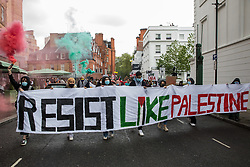 Protesters walk behind a banner holding smoke grenades during a Free Palestine SOS Colombia march in solidarity with the Palestinian and Colombian peoples from the Colombian embassy to the Israeli embassy on 15th May 2021 in London, United Kingdom. Speakers at a rally before the march, which took place on Nakba Day, highlighted human rights abuses being directed against Palestinians in Israel and the Occupied Territories, in particular attempts at forced displacements in Sheikh Jarrah in East Jerusalem, and also in Colombia, where peaceful demonstrators and human rights defenders have been killed and subjected to repression, detention and torture.
