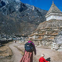 Meredith Wiltsie & 3-year old son Ben walk past a Tibetan Buddhist chorten while trekking  in the Khumbu Region of Nepal,.