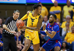 Feb 12, 2020; Morgantown, West Virginia, USA; West Virginia Mountaineers forward Gabe Osabuohien (3) looks to pass while defended by Kansas Jayhawks guard Isaiah Moss (4) during the first half at WVU Coliseum. Mandatory Credit: Ben Queen-USA TODAY Sports