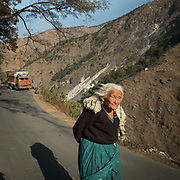 A tibetan woman walking on the road with truck. In the Himalaya.