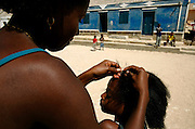 Girls treating their hair on the main street of Barranco Velho where there are some examples of simple popular architecture. As in most of Cape Verde archipelago, facades are colorfully painted.