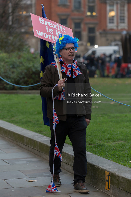 Carrying a placard asking if Brexit is worth it, a pro-EU remainer waks alongside College Green opposite the Houses of Parliament at a time of crisis for the country when Prime Minister Theresa May deals with Brexit negotiations and minister resignations, on 15th November 2018, in London, England.