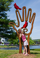 """Sisters Alayna and Faith Bond from Franklin, MA meandering through Meredith stop at """"Bird in Hand"""" by Dale Rogers of Haverhill, MA as part of the Sculpture Walk on Sunday afternoon.  (Karen Bobotas/for the Laconia Daily Sun)"""