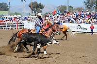 Wade Wheatley from Hughson, CA and his partner Todd Hampton from Chowchilla, CA put the first touch on a calf in the team roping competition at the 102nd California Rodeo Salinas, which opened July 19 for a four-day run.