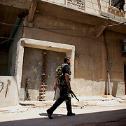 August 09, 2012 - Aleppo, Syria: A Free Syria Army (FSA) fighter leaves the headquarters in Haneno neighborhood, to join his comrades on the frontline at Salehedine...The Syrian army and the FSA have in the past week exchanged heavy fire in a battle for the control of Syria's economic capital, Aleppo.