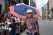 New York, NY - 30 June 2019. The New York City Heritage of Pride March filled Fifth Avenue for hours with participants from the LGBTQ community and it's supporters. David 88, marches under a stars and stripes parasol.
