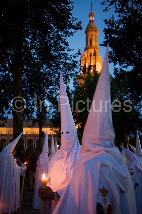 Hooded penitents (Nazarenos) in candlelit procession during Seville's annual Easter Holy Week (Semana Santa de Sevilla) one of the most important traditional events of the city. The annual celebrations mark the story of Christ's crucifixion and the Nazarenos walk through the historic Andalucian city in front of the devout in a series of processions. Several hundred members of the 57 religious brotherhoods (or Hermandades) from many of city churches accompany giant floats (Pasos) depicting the road to Calvary. <br /> The brotherhoods (founded in the mid 14th century) are associations of Catholic laypersons organised for the purpose of performing public acts of religious observance; in this case, related to the Passion and death of Jesus Christ and to perform public penance.