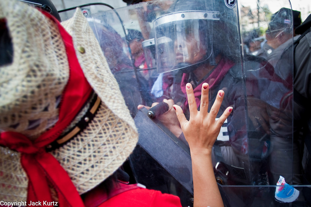 Apr. 12, 2010 - BANGKOK, THAILAND: A Red Shirt woman pleads with Thai riot police in front of the Prime Minister's house on Soi 31 off of Sukhumvit Rd in Bangkok Monday. The funeral cortege for the Red Shirts killed in the violent crackdown Saturday wound through Bangkok and parts of the procession passed by the Prime Minister's home. Thousands of mourners came out to pay respects for dead Red Shirts. 21 people, including 16 Thai civilians were killed when soldiers tried to clear the Red Shirts' encampment in Bangkok. Thousands more came out to call for the government of Thai Prime Minister Abhisit Vejjajiva to step down. Today Gen. Anupong Paojinda, the Chief of Staff of the Thai Army, reiterated that the Army would not use violence to break up the protests and joined the call for the Prime Minister to call new elections. This is the beginning of Songkran, Thai New Year's week, and the government has cancelled the official festivities fearing more violence. It was during last year's Songkan festivities that the Thai Army and police used force to break up the Red Shirt protests. That protest is now called the Songkran Riots.         Photo By Jack Kurtz