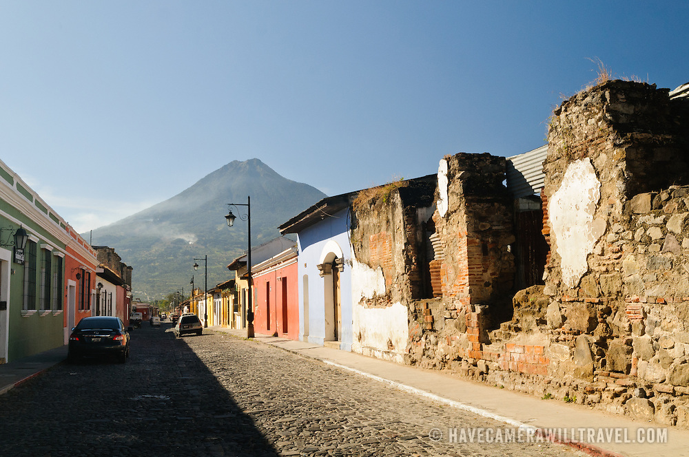 Traditional Spanish colonial architecture of Antigua stands in the foreground, with Volcán de Agua (or Agua Volcano) towering in the background. Famous for its well-preserved Spanish baroque architecture as well as a number of ruins from earthquakes, Antigua Guatemala is a UNESCO World Heritage Site and former capital of Guatemala.