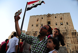 (170729) -- ALEPPO (SYRIA), July 29, 2017 (Xinhua) -- Syrian people take a selfie near the ancient citadel of Aleppo city in northern Syria on July 28, 2017. The rebels had stayed in the east of Aleppo for five years before they evacuated in December of 2016. Seven months after the Syrian army took full control over the city, life starts to beat again through devastation and destruction in the area. (Xinhua/Ammar Safarjalani) (zjy) (Photo by Xinhua/Sipa USA)