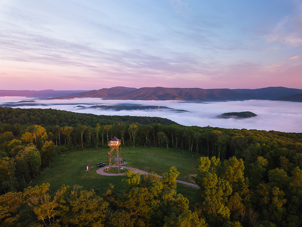 Fog flows through the Greenbrier River Valley exposing mountain top islands to the morning sun around the Thorny Mountain Fire Tower in West Virginia.