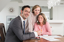 Smiling consultant and mature and young woman at home