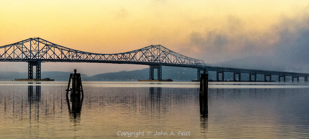 The sun is starting to show onto the Hudson River at Tarrytown, NY, creating a glow in the waning fog and silhouetting the Tappan Zee Bridge.