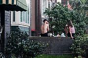 A young man and young woman enjoy a picnic on their garden wall outside their Bondi Apartment, Bondi Beach, Sydney, Australia.