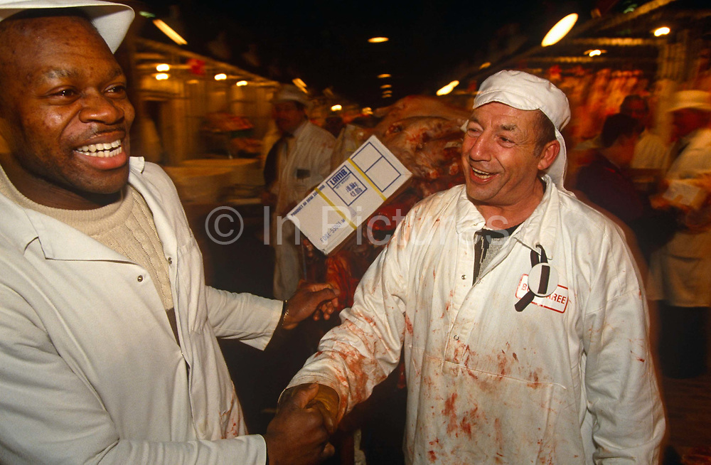 Amid much humour and banter, two meat porters grab hands in Smithfield market during the pre-dawn buying and selling of meat, bought and sold here for 800 years, one of London's oldest markets. One man's coat reveals blood stains as he smiles good-naturedly to his fellow worker who is of afro-Caribbean descent. A livestock market occupied the site as early as the 10th century. Approximately 120,000 tons of produce pass through the market each year. As well as meat and poultry, products such as cheese, pies, and other delicatessen goods are available. Buyers including butchers, restaurateurs and caterers are able see the goods for themselves and drive away with what they have bought. Bargaining between buyers and sellers at Smithfield sets the guidelines for meat and poultry prices throughout the UK.
