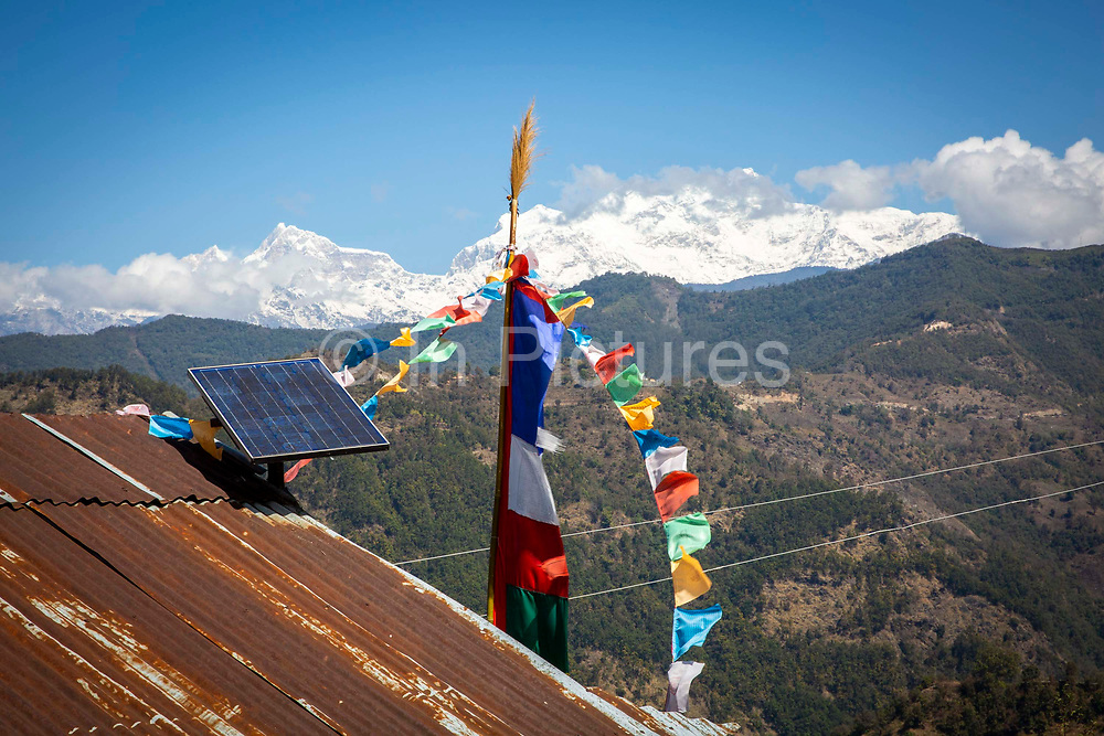 A solar panel and traditional Nepali flags in front of the Mansiri Himal mountain range and Himalchuli mountain on the 6th of March 2020 in the Mansiri Hilam subrange of the Himalayas in North Central Nepal.  Himalchuli is the second highest mountain in the Mansiri Himal, part of the Nepalese Himalayas.