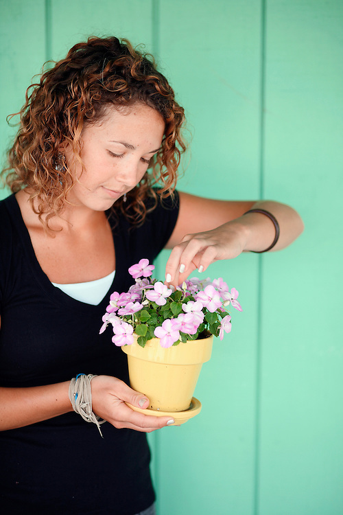 Sasha B. holds a plant with flowers
