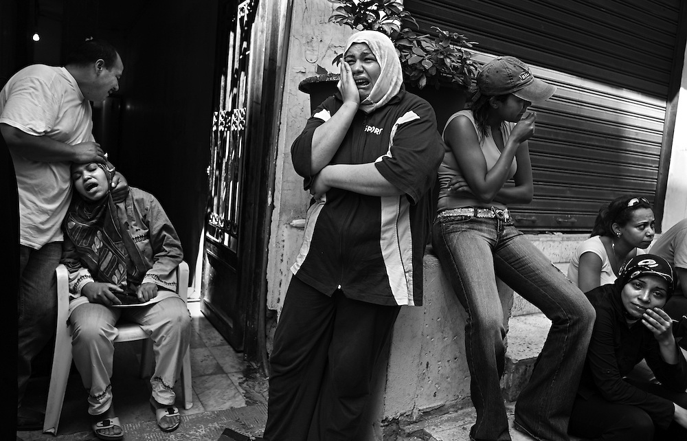 Family members wail in grief after learning of the death of Ahmad Kange, 13, who died the previous night when an apartment building was hit by an Israeli raid, in Beirut, Lebanon, Aug. 8, 2006. Ahmad left his home, one block from the scene, to get an ice cream cone when he was killed. The attack, which took place in the residential neighborhood of Chiyah, killed more than 2 dozen people and wounded scores more. The Kange family were not Hezbollah supporters but Amal supporters, the rival Shia group in Lebanon.
