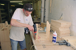 Cabinet maker using drill to construct carcass of bedside cabinet,