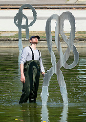 © Licensed to London News Pictures. 27/07/2018. London, UK. A worker wearing waders inspects a water sculpture in Battersea Park. Rain is expected later to break the heatwave in parts of the south. Photo credit: Peter Macdiarmid/LNP