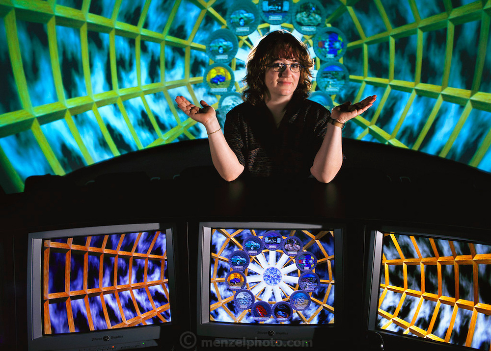 Silicon Valley, California; Linda Jacobson, Virtual Reality Evangelist at Silicon Graphics, Incorporated, Mountainview, California. Jacobson stands poised over the operations area of one of Silicon Graphics' RealityCenters. The high tech console operates the large wrap-around screen behind her. Jacobson's dream is to be the host of a virtual reality talk show. In the meantime, this former Wired Magazine reporter is content to tout the virtues of Immersive Visualization?the newly coined industry name, she says, for virtual reality. The tangible element of her job at SGI is to manage and market SGI's RealityCenters?facilities designed to do quick representations in a fully interactive graphical interface. These can include virtual factory tours; automobile mock-ups; and mock-up product changes depending on the desires of purchasing company. Model Released (1999).