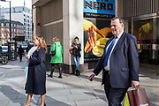 London street scene on Victoria Street, London, United Kingdom.  People wait and walk past a Cafe Nero coffee shop.