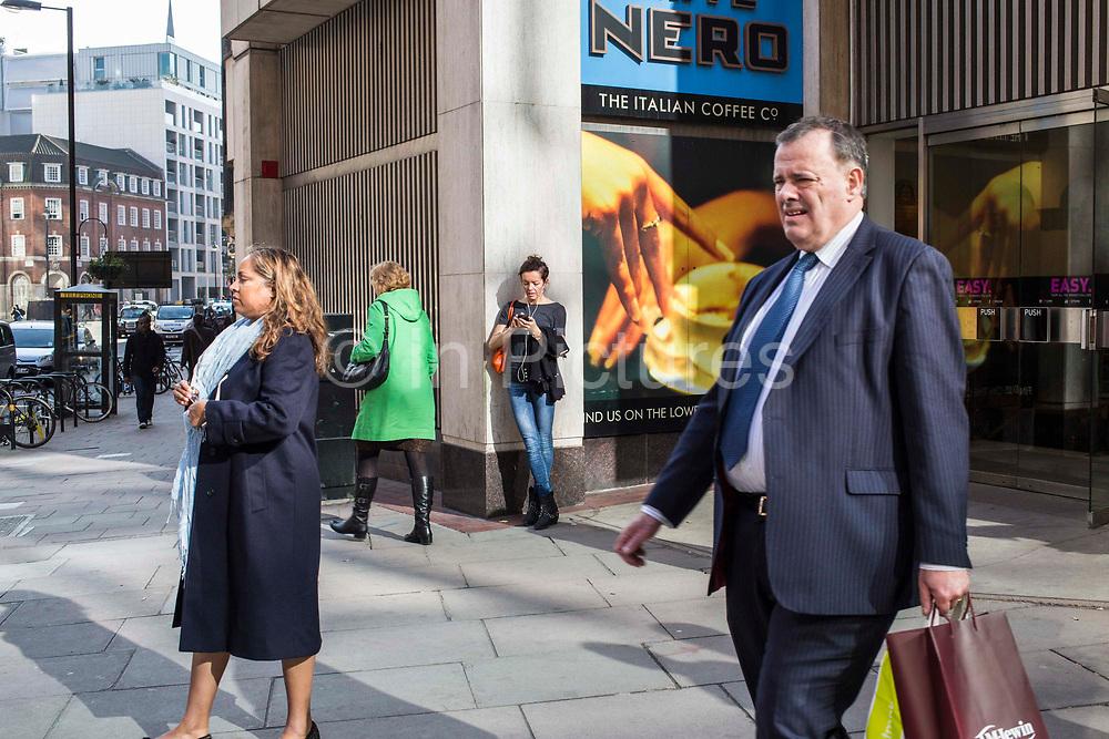London street scene on Victoria Street, London, United Kingdom.  People wait and walk past a Cafe Nero coffee shop.