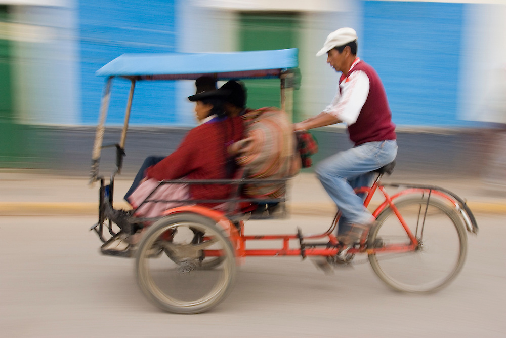 Bicycle rickshaw driver with 2 passengers in Sicuani, Peru, South America (panned motion)
