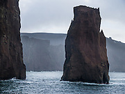 A sea stack of volcanic ash erodes from a cliff at Deception Island in the Southern Ocean (also called the Antarctic Ocean). Port Foster is one of the safest harbors in Antarctica, once you pass through narrow Neptune's Bellow (just 230 meters or 755 feet wide), sole entrance to the sea-filled caldera of Deception Island, in the South Shetland Islands near the Antarctic Peninsula. Deception Island is the caldera of an active volcano, which caused serious damage to local scientific stations in 1967 and 1969. The island previously held a whaling station and is now a tourist destination and scientific outpost, with research bases run by Argentina and Spain. The island is administered under the Antarctic Treaty System. The surrounding Southern Ocean (Antarctic Ocean) is closed by ice from early April to early December. Whalers Bay is bordered by a large black-sand beach.