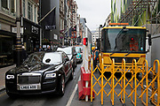 New Rolls Royce car pulls up alongside a large lorry at a construction site on Bond Street in London, England, United Kingdom. Bond Street is one of the principal streets in the West End shopping district and is very upmarket. It has been a fashionable shopping street since the 18th century. The rich and wealthy shop here mostly for high end fashion and jewellery.