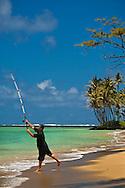Fisherman casting from the shore at Punalu'u Beach Park, Oahu, Hawaii