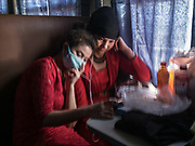 Two girls watch a movie. Life inside the train - mostly Muslim Uighur people  ride this train.