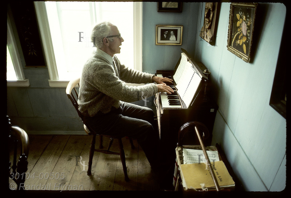 Thord Tomasson, director of Skogar folk museum, plays an old organ in museum's sitting-room. Iceland