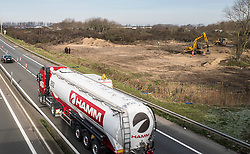 © London News Pictures. Calais, France. 18/01/16. A lorry drives past bulldozers clearing up to 1/3 of the Calais 'Jungle' refugee camp. French authorities are clearing a 100-metre 'buffer zone' between the camp and the adjacent motorway, which leads to the ferry port.  Photo credit: Rob Pinney/LNP